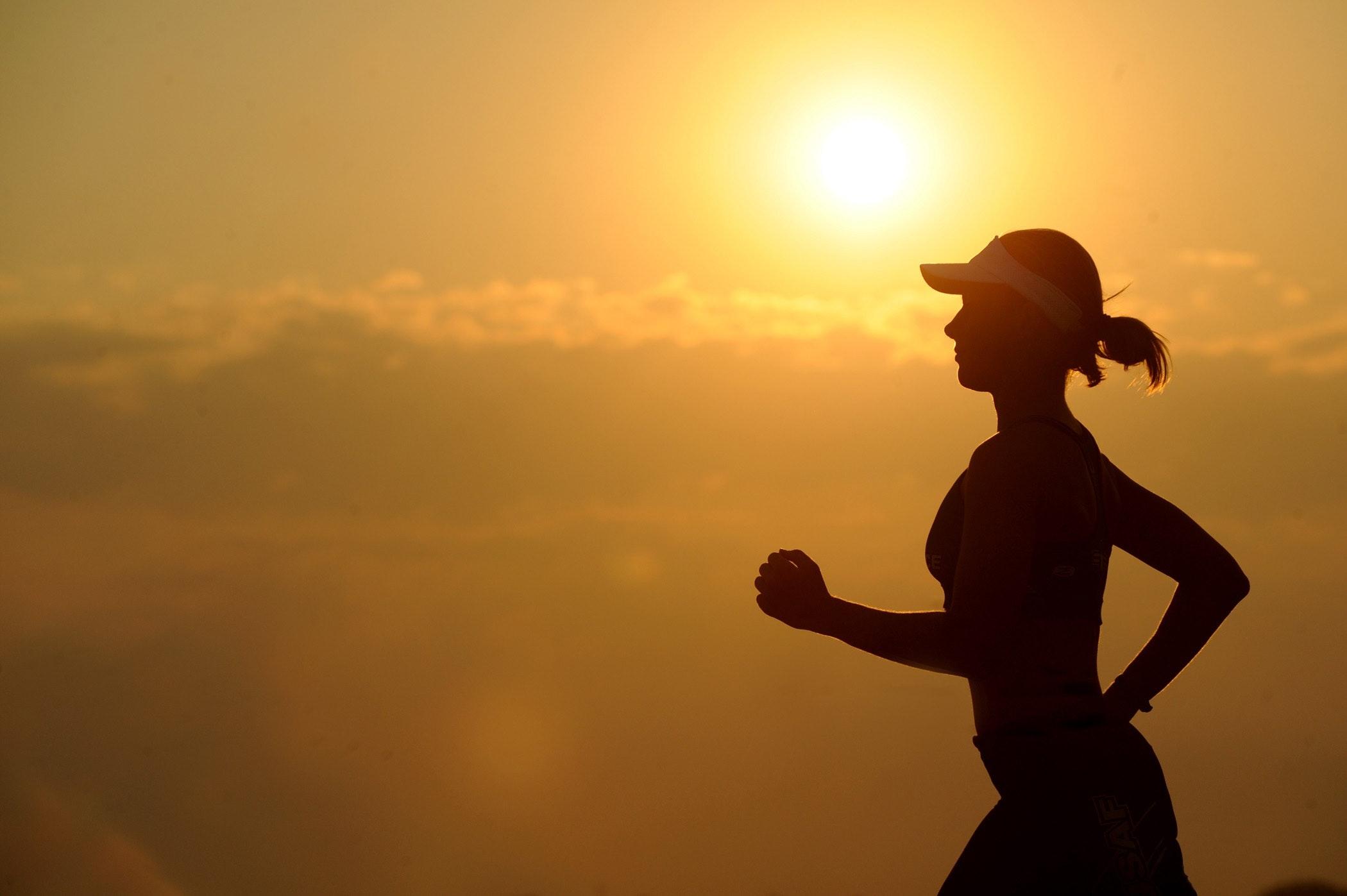 Ung kvinne løper i soloppgang